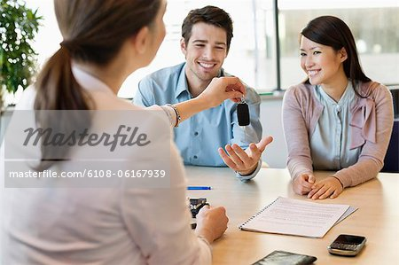 Couple receiving keys from business executive Stock Photo - Premium Royalty-Free, Image code: 6108-06167939