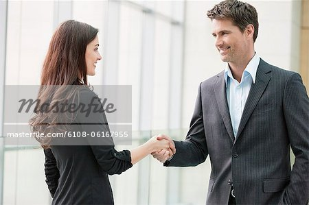 Business executives shaking hands in an office Stock Photo - Premium Royalty-Free, Image code: 6108-06167955