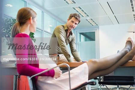 Pregnant woman talking to her colleague in the office Stock Photo - Premium Royalty-Free, Image code: 6108-06168018