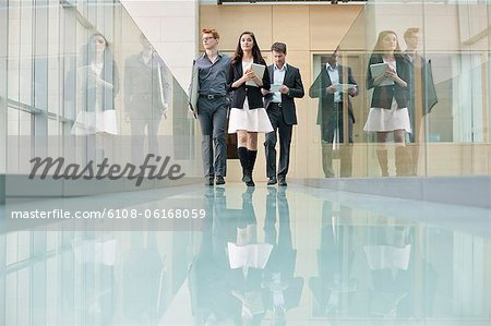 Business executives walking in a corridor Stock Photo - Premium Royalty-Free, Image code: 6108-06168059