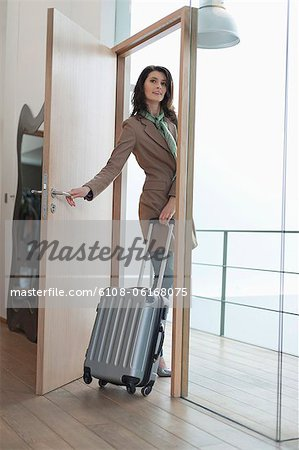 Woman closing the door of a house Stock Photo - Premium Royalty-Free, Image code: 6108-06168075