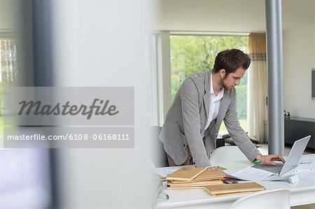 Interior designer working on a laptop in the office Stock Photo - Premium Royalty-Free, Image code: 6108-06168111