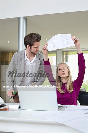 Woman examining an architectural design in the office Stock Photo - Premium Royalty-Free, Image code: 6108-06168119