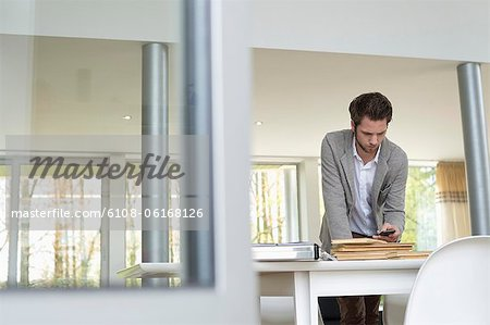 Interior designer using a mobile phone in the office Stock Photo - Premium Royalty-Free, Image code: 6108-06168126