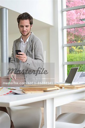 Interior designer using a mobile phone in the office Stock Photo - Premium Royalty-Free, Image code: 6108-06168141