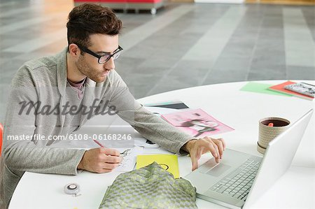 Male fashion designer working in an office Stock Photo - Premium Royalty-Free, Image code: 6108-06168246