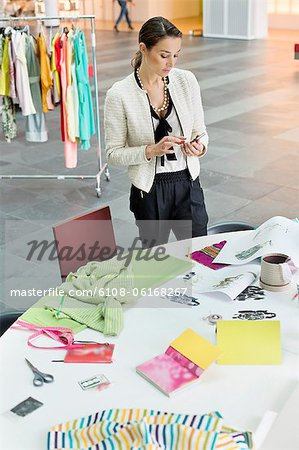 Female fashion designer text messaging in an office Stock Photo - Premium Royalty-Free, Image code: 6108-06168267