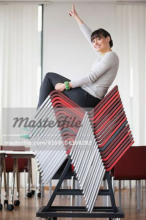 Businesswoman sitting on pileup chairs in an office Stock Photo - Premium Royalty-Free, Image code: 6108-06168282