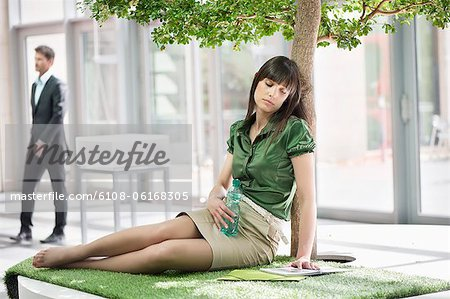 Businesswoman relaxing on grass mat Stock Photo - Premium Royalty-Free, Image code: 6108-06168305