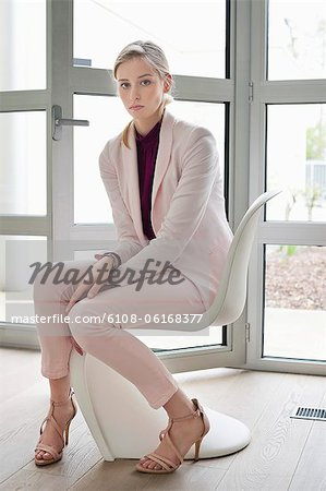 Businesswoman sitting on a chair Stock Photo - Premium Royalty-Free, Image code: 6108-06168377