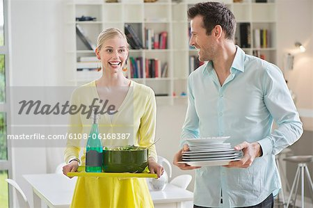 Couple carrying plates and food for serving Stock Photo - Premium Royalty-Free, Image code: 6108-06168387