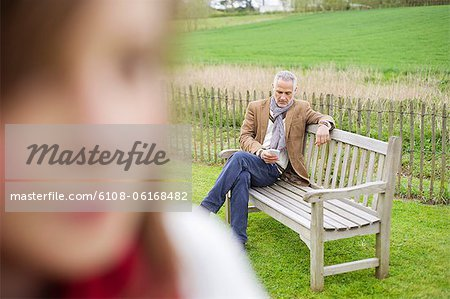 Close-up of a girl with her father text messaging in the background Stock Photo - Premium Royalty-Free, Image code: 6108-06168482