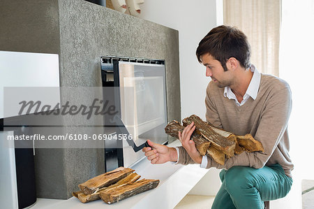 Man putting firewood into a fireplace Stock Photo - Premium Royalty-Free, Image code: 6108-06904536