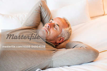 Man resting on the bed in a hotel room Stock Photo - Premium Royalty-Free, Image code: 6108-06904538