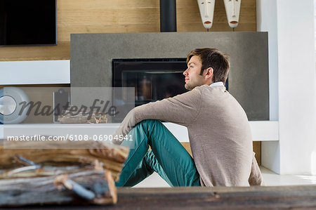 Man sitting in front of a fireplace at home Stock Photo - Premium Royalty-Free, Image code: 6108-06904541