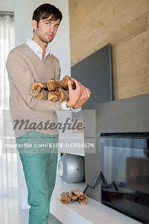 Portrait of a man carrying firewood Stock Photo - Premium Royalty-Free, Image code: 6108-06904574