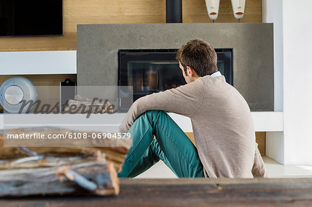 Man sitting in front of a fireplace at home Stock Photo - Premium Royalty-Free, Image code: 6108-06904579