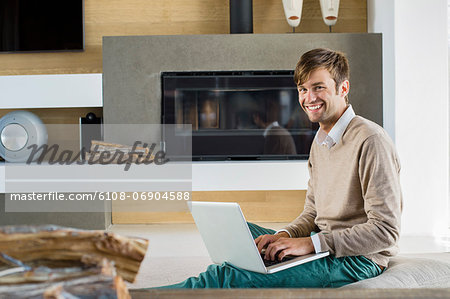Portrait of a smiling man using a laptop Stock Photo - Premium Royalty-Free, Image code: 6108-06904588