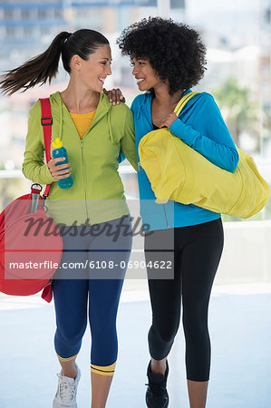 Two happy female friends carrying gym bags Stock Photo - Premium Royalty-Free, Image code: 6108-06904622
