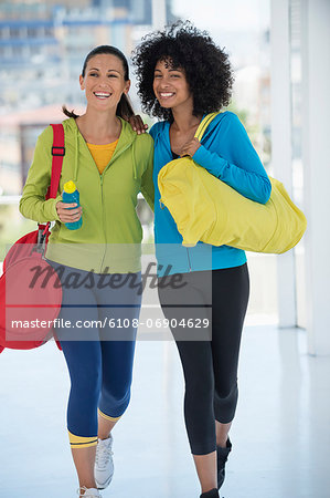 Two happy female friends carrying gym bags Stock Photo - Premium Royalty-Free, Image code: 6108-06904629