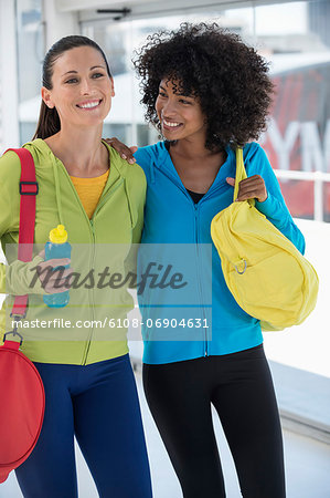 Two happy female friends carrying gym bags Stock Photo - Premium Royalty-Free, Image code: 6108-06904631