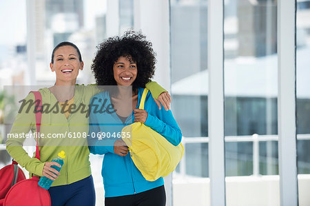 Two happy female friends carrying gym bags Stock Photo - Premium Royalty-Free, Image code: 6108-06904635