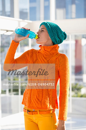Woman drinking water from a bottle Stock Photo - Premium Royalty-Free, Image code: 6108-06904732