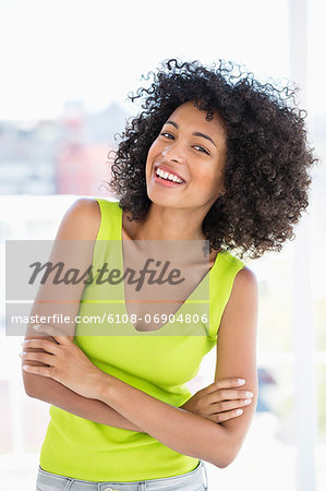 Woman standing with her arms crossed and smiling Stock Photo - Premium Royalty-Free, Image code: 6108-06904806