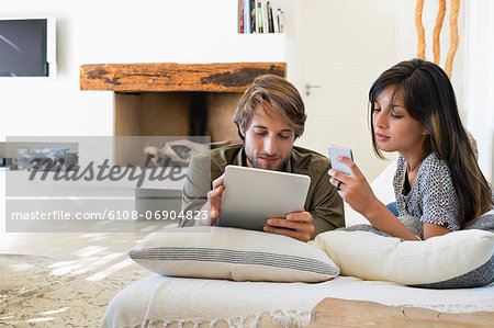 Couple lying on the bed and using electronic gadgets Stock Photo - Premium Royalty-Free, Image code: 6108-06904823