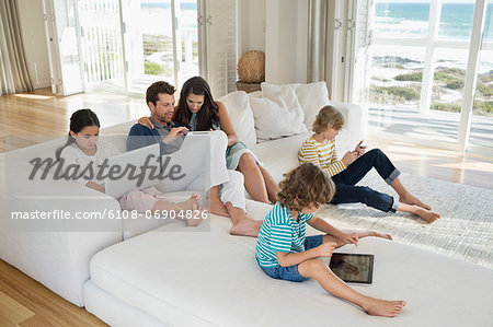 Family using electronic gadgets in a living room Stock Photo - Premium Royalty-Free, Image code: 6108-06904826