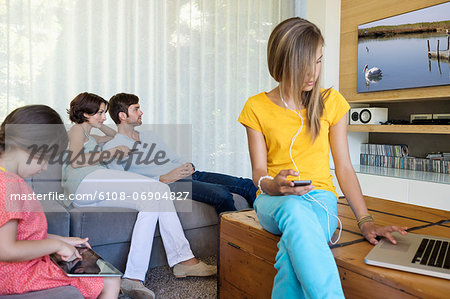 Family using electronics gadgets Stock Photo - Premium Royalty-Free, Image code: 6108-06904827