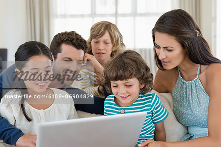 Family looking at a laptop Stock Photo - Premium Royalty-Free, Image code: 6108-06904829