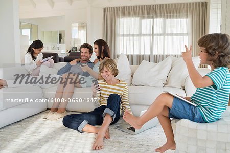 Family using electronics gadget Stock Photo - Premium Royalty-Free, Image code: 6108-06904847