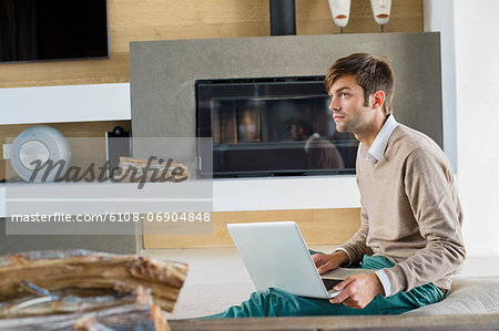 Man using a laptop at home Stock Photo - Premium Royalty-Free, Image code: 6108-06904848