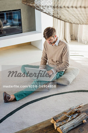 Man using a laptop at home Stock Photo - Premium Royalty-Free, Image code: 6108-06904858