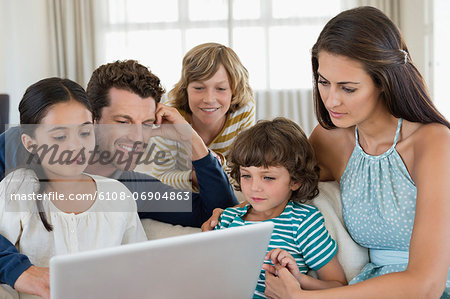 Family looking at a laptop Stock Photo - Premium Royalty-Free, Image code: 6108-06904863