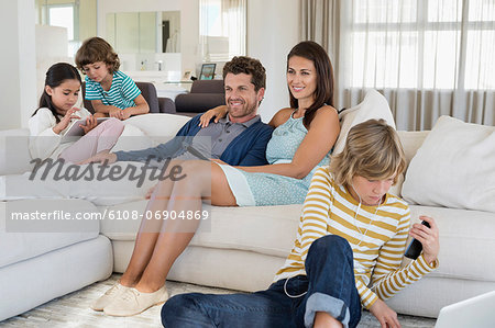 Family using electronics gadget Stock Photo - Premium Royalty-Free, Image code: 6108-06904869