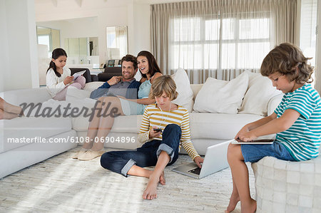 Family using electronics gadget Stock Photo - Premium Royalty-Free, Image code: 6108-06904896