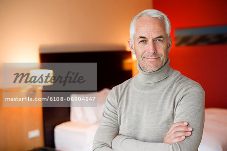 Portrait of a man smiling with arms crossed in a hotel room Stock Photo - Premium Royalty-Free, Image code: 6108-06904947