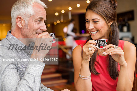 Couple enjoying cup of tea in a restaurant Stock Photo - Premium Royalty-Free, Image code: 6108-06904987