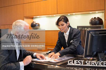 Receptionist showing a brochure to a businessman at a hotel reception counter Stock Photo - Premium Royalty-Free, Image code: 6108-06904994