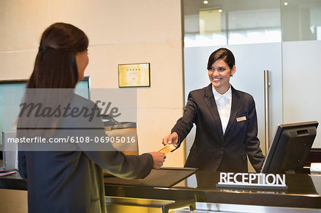 Businesswoman paying with a credit card at the hotel reception counter Stock Photo - Premium Royalty-Free, Image code: 6108-06905016