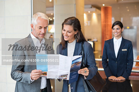 Business couple reading a brochure in front of a hotel reception counter Stock Photo - Premium Royalty-Free, Image code: 6108-06905021