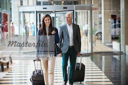Business couple pulling suitcases in a hotel lobby Stock Photo - Premium Royalty-Free, Image code: 6108-06905031