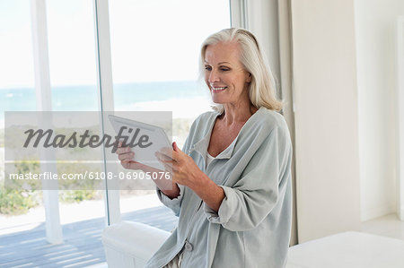 Woman using a digital tablet and smiling at home Stock Photo - Premium Royalty-Free, Image code: 6108-06905076