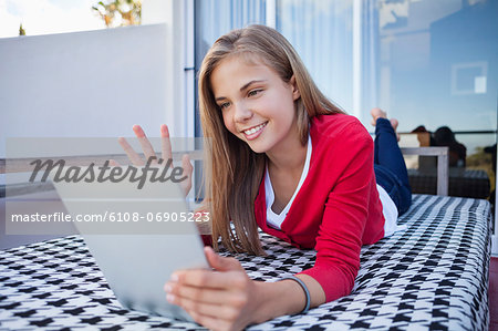 Girl lying on the bed and video chatting on a digital tablet Stock Photo - Premium Royalty-Free, Image code: 6108-06905223