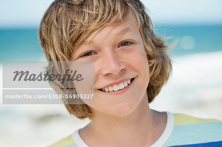 Portrait of a boy smiling on the beach Stock Photo - Premium Royalty-Free, Image code: 6108-06905227