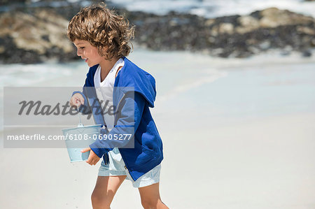 Boy playing on the beach Stock Photo - Premium Royalty-Free, Image code: 6108-06905277