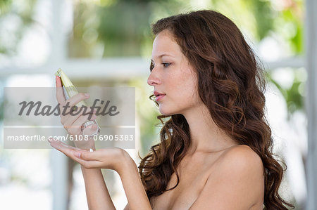 Woman holding a moisturizer bottle Stock Photo - Premium Royalty-Free, Image code: 6108-06905383