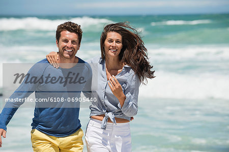 Couple enjoying on the beach Stock Photo - Premium Royalty-Free, Image code: 6108-06905440